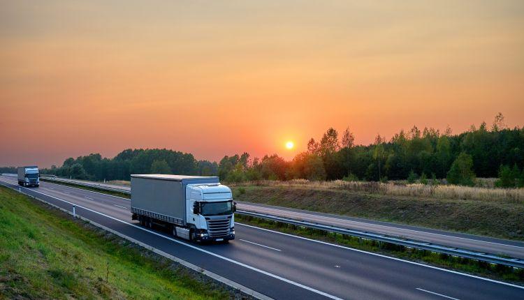 White,Trucks,Driving,On,The,Asphalt,Highway,In,The,Landscape